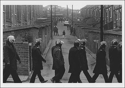 The greetings card oshowing a young woman returning home at lunchtime from her job at Hintons, the grocers. Police line the alleyway down which she is walking and a line of marching police officers pass the end of the alleyway.