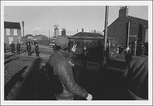 Greetings card of pickets gestitulacing to working miners in a coach on Station Road, Easington Colliery, County Durham, during February 1985.