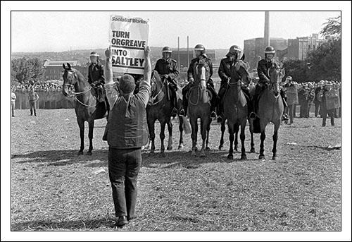 """Postcard of a picket holding placard reading """"Turn Orgreave into Saltley"""" on 18th June 1984."""